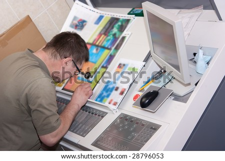 Printer checking a print run at table