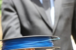 Printer filament held in hand by man in suit showing industry business concept. PLA filament made from renewable resources which is kind of thermoplastic