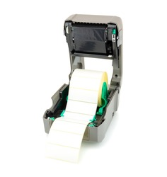 Printer with ribbon and white label roll isolated on white background with shadow reflection. White reel of labels and printer. Studio picture showing thermal transfer print setup. Close-up shot.