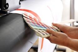 Printing machine, color print. The printer checks the color of the printout on the color sampler.