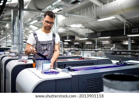 Printing machine operator preparing paint for print process in printing house. Photo stock ©