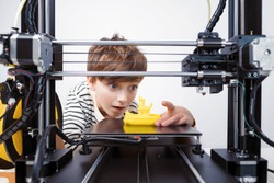 Printing on 3D printer figurines of toys from white plastic close-up. Boy happily and emotionally takes the finished printed figure from the working platform of the printer and goes into the play