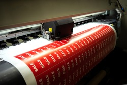 Printing stickers with the inscription sale on the printing press. Preparing for the night of sales in hypermarkets