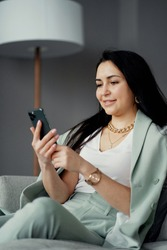 prints a new message text in the phone, communicates in a work chat. experienced manager confident young woman brunette of European appearance smiling sitting on a sofa in a modern office.