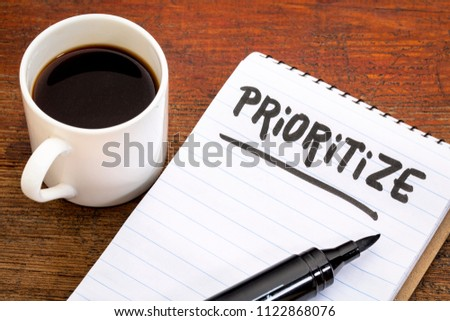 prioritize advice or reminder - handwriting oin a spiral notebook with a cup of coffee