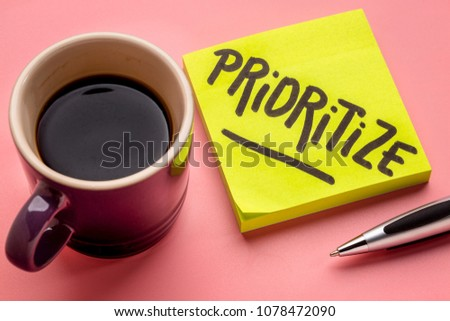 prioritize advice or reminder - handwriting on a sticky note with a cup of coffee