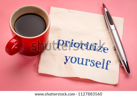 prioritize yourself advice - handwriting on a napkin with a cup of espresso coffee