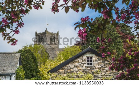 Priory peeping above rooftops with green foilage and flowers. Taken on a sunny day with blue sky. Cartmel, Cumbria. Stock photo ©