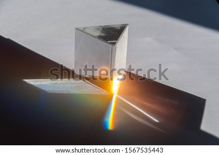 prism dispersing sunlight splitting into a spectrum on a white background.