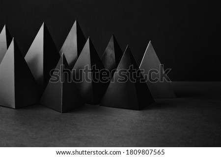Photo of  Prism pyramid objects on black gray background. Abstract geometrical figures still life composition