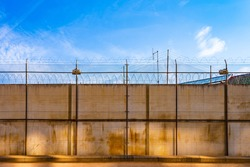Prison area surrounded with fence and blue sky in the background. Concrete wall, against the backdrop of barbed wire, the concept of prison, salvation, refugee, lonely. Barbed wire fence detail.