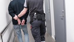 Prison guard escort arrested inmate through jail corridor