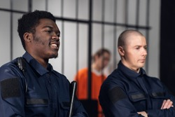 Prison guards smile as they stand with batons near cells with dangerous criminals. Multi-racial portrait
