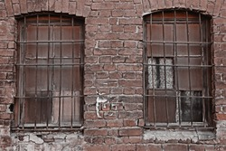 prison. imprisonment. incarceration, jail time. gaol. old brick wall .window with bars. vintage grim building. cell. western