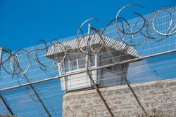 Prison Scene with razor wire foreground and guard tower in background.  Location old Fremantle Prison Western Australia.  Security fencing with razor wire watch tower.