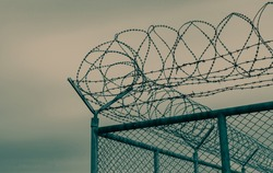 Prison security fence. Barbed wire security fence. Razor wire jail fence. Barrier border. Boundary security wall. Prison for arrest criminals or terrorists. Private area. Military zone concept.
