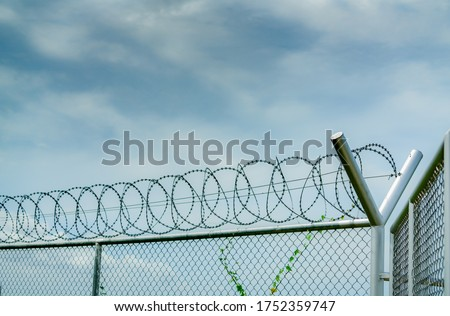 Prison security fence. Barbed wire security fence. Razor wire jail fence. Barrier border. Boundary security wall. Prison for arrest criminal or terrorist. Private area. Military zone concept.