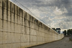 Prison wall and concertina in cloudy day.