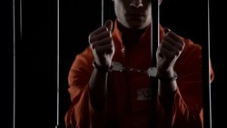 Prisoner in orange uniform showing handcuffs, looking angry and disappointed