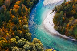 Pristine alpine turquoise river meandering through forested landscape in a sunny autumn day, aerial view. Pristine, clean nature, pure water, environment concept.