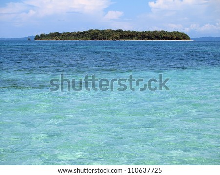 Pristine tropical island at the horizon with turquoise water in foreground