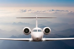 Private Airplane fly over clouds and Alps mountain on sunset. Front view of a big passenger or cargo aircraft, business jet, airline. Transportation, travel concept