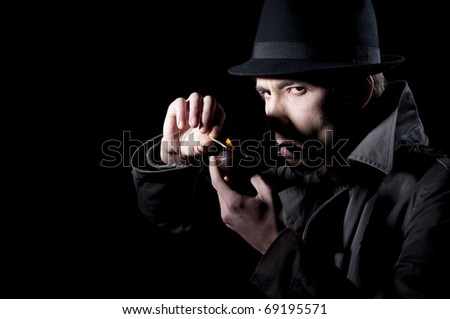 Private detective lighting his pipe, isolated on a black background