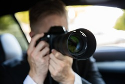 Private Detective Sitting Inside Car Doing Surveillance Work Photographing With Camera