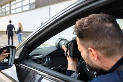 Private Detective Taking Photos Of Man And Woman On Street