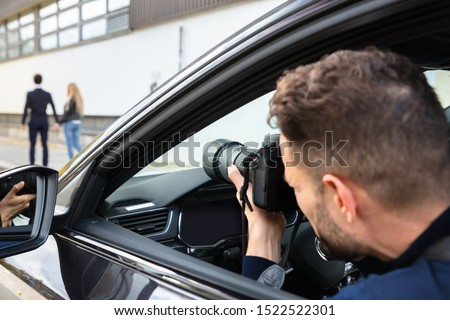 Private Detective Taking Photos Of Man And Woman On Street Stockfoto ©