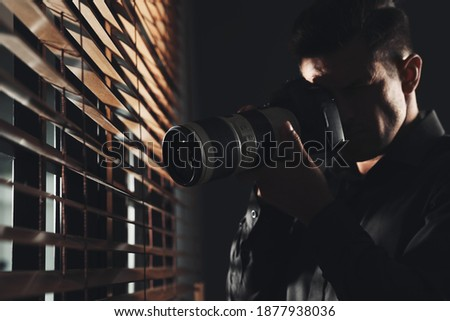 Private detective with camera spying near window indoors Сток-фото ©