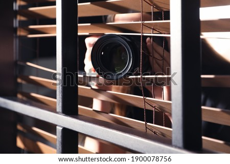 Private detective with camera spying near window indoors, closeup Foto stock ©