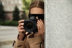 Private detective with modern camera spying outdoors, focus on lens