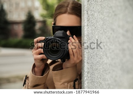 Private detective with modern camera spying outdoors, focus on lens Сток-фото ©