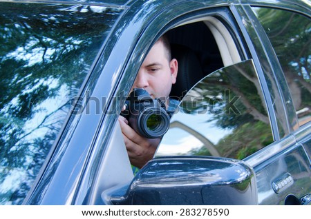 Private investigator on a stakeout is photographing the situation to document the events.