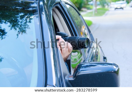 Private investigator on a stakeout is photographing the situation to document the events with a camera sticking out of a car window.
