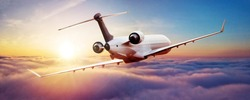 Private jet plane flying above clouds in beautiful sunset light. Modern and fastest mode of transportation, business life