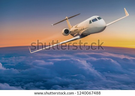 Private jet plane flying above dramatic clouds during sunset.