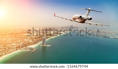Private jet plane flying above Dubai city in beautiful sunset light. Modern and fastest mode of transportation, business life.