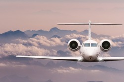 Private Jet plane over clouds and Alps mountain on sunset. Front view of a big passenger or cargo aircraft, business jet, airline. Travel concept. Empty space for text