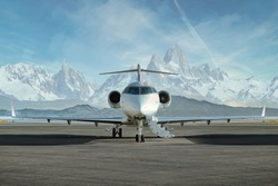 Private jet waiting to be boarded on runway with snowy mountains in the background