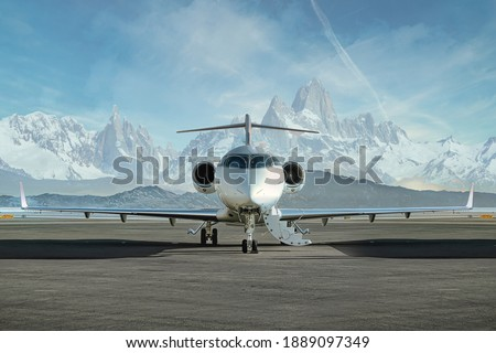 Private jet waiting to be boarded on runway with snowy mountains in the background Photo stock ©