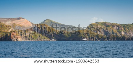 Private motor yacht motoring past the island of Volcano in the Aeolian islands of Italy, with the volcano in the background, impressive rocky coastline with vegetation and blue sky. #1500642353