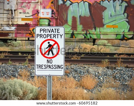 private property no trespassing sign with graffiti covered train in background