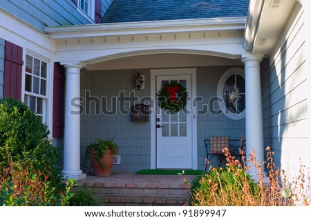 Private residence front porch and entrance adorned with Christmas wreath