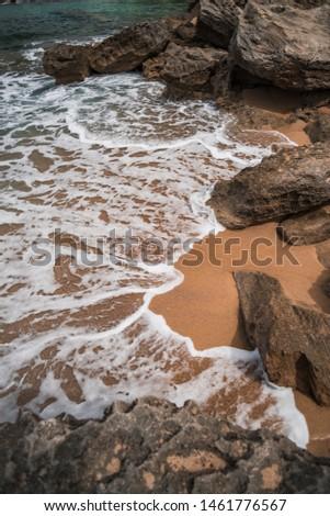 Private sand beach on Sardinia Island, little beach, small paradise in Sardegna. Sea foam comes over the sand. Sea wave splashes on the sand. Sandy coast, shoreline of Italy.