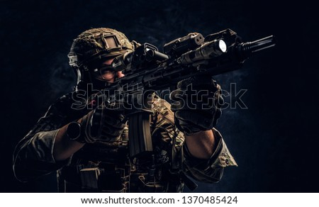 Private security service contractors, the elite special unit, full protective soldier holding assault rifle aiming at the target. Studio photo against a dark wall. #1370485424