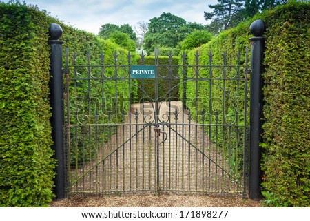 Private sign attached to an ornate wrought iron gate leading int