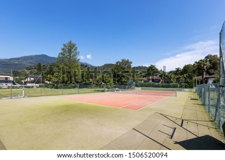 Private tennis court on a beautiful sunny summer day. Nobody inside #1506520094
