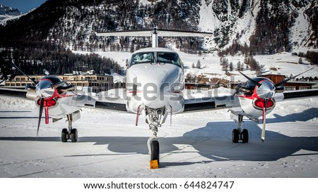 Private turbo propeller aircraft parked over snow. Frontal shot during taxiing to runway. Bizjet, airplane for VIP and luxury. Airport over Alps with a small city as background.